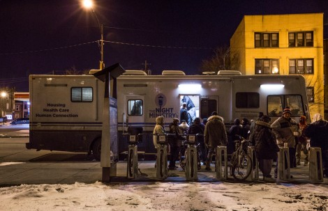 Needy members of the Humboldt Park community wait patiently for food, supplies and health care services outside the Health Outreach bus.