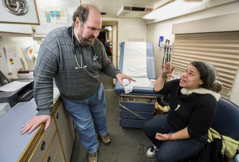 Matthew Sorenson examines Magdeline Cruz (note spelling) inside the Night Ministry's Health Outreach Bus during a stop Tuesday, Jan. 27, 2015 at Humboldt Park in Chicago. Cruz credits the Night Ministry organization for getting her off the streets and providing her healthcare she cannot afford. Sorenson is the associate director, Master's Entry to Nursing Practice Program at the College of Science and Health. (DePaul University/Jamie Moncrief)