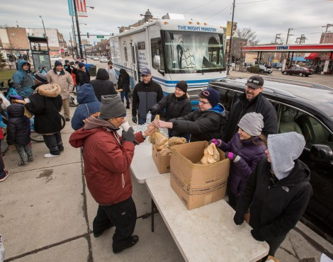 Members of the First Congregational Church of Western Springs hand out bag lunches near The Night Ministry's Health Outreach bus during a Sunday afternoon stop.