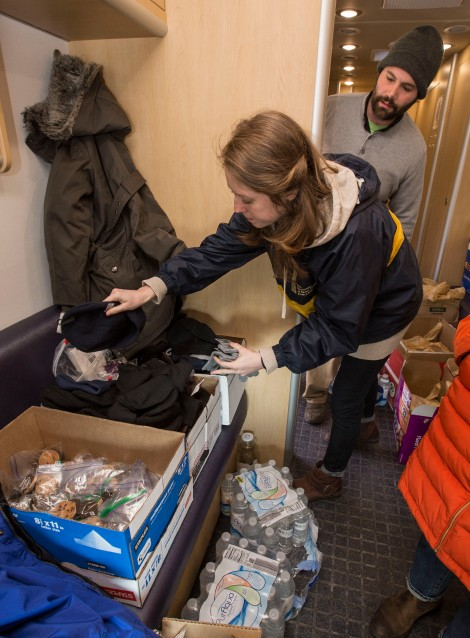 Matt Holmes (CDM '14) and Melanie Fritz go through their supplies of food, beverages and outerwear to help fortify those in need against the harsh winter weather.