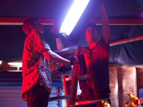 Key grip Sam Condon and electrician Will Brunker (DEGREE) rig a Kino light to the ceiling for the Hawaiian party scene. Photo credit: James Psathas