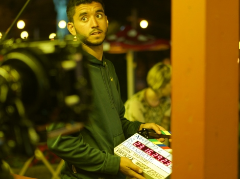 Second assistant camera Josue Ortiz gets ready to clap the slate on location at the carnival. Photo credit: James Psathas