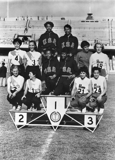Flanked by the second and third place winners, the United States team that won the women's 400-meter relay event at the Pan-American games in Mexico City Occupies the honor spot on the winners' pedestal. The American girls are (standing) Isabel Daniels (Left) and Mabel Landry. Kneeling: Mae Faggs and Barbara Jones. The Argentine team at left is composed of (Stadning) Maria Ostelli (left) and Glady's Erbetta, kneeling: Lilian Buglia and Lilian Heinz. The Chilean team at right, which won 3rd place is composed of (standing) Beatriz Kreefchler and Carmen Vengas and (Kneeling) Eleana Gaete and Elda Selene. Photo credit: Getty Images