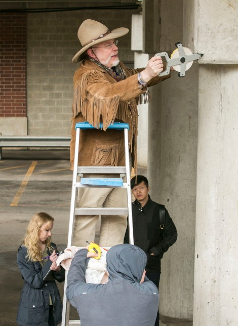 Brother Mark Elder, C.M., measures the support columns underneath the CTA's Fullerton 'L' stop during his class 'Mural Painting', Friday, April 1, 2016. Throughout the spring 2016 quarter and into the summer, Br. Mark and his students will create several murals that will wrap the support columns underneath the CTA's Fullerton 'L' stop, which runs right through DePaul's Lincoln Park Campus. The murals will depict many prominent, historical figures that have made an impact on DePaul University. (DePaul University/Jamie Moncrief)