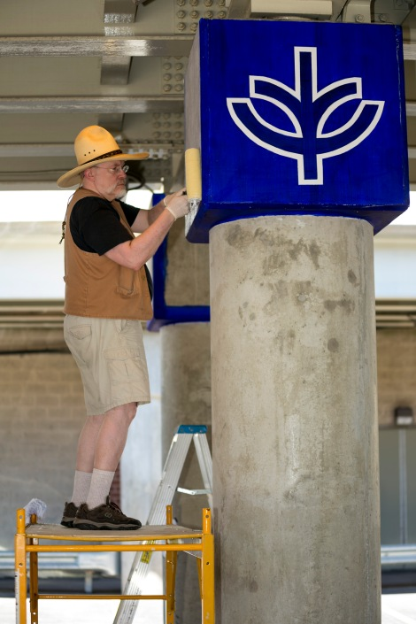 "Brother Mark Elder, C.M., hangs a series of murals Saturday, Aug. 6, 2016, on the massive concrete pillars supporting the CTA's ""L"" station and tracks at Fullerton. Throughout the spring 2016 quarter and into the summer, Brother Mark and his Mural Class students created several portraits and historically-themed murals that will eventually wrap the support columns, which runs right through DePaul's Lincoln Park Campus. The murals depict many prominent, historical figures that have made an impact on DePaul University. (DePaul University/Joel Dik)"