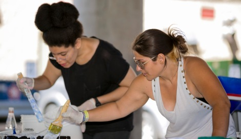 "Christina Morris, left, and Joanna Geordano, right, both former DePaul students, help Brother Mark Elder, C.M., hang a series of murals Saturday, Aug. 6, 2016, on the massive concrete pillars supporting the CTA's ""L"" station and tracks at Fullerton. Throughout the spring 2016 quarter and into the summer, Brother Mark and his Mural Class students created several portraits and historically-themed murals that will eventually wrap the support columns, which runs right through DePaul's Lincoln Park Campus. The murals depict many prominent, historical figures that have made an impact on DePaul University. (DePaul University/Joel Dik)"