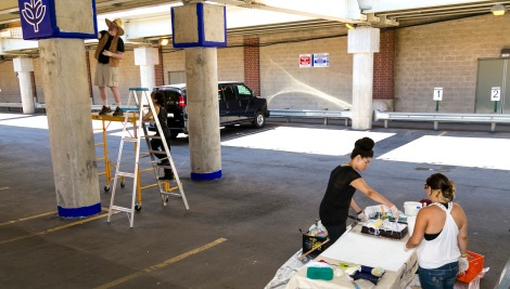 "Brother Mark Elder, C.M., with the aid of former DePaul students Emanuel Cajijas, Christina Morris, and Joanna Geordano, hangs a series of murals, Saturday, Aug. 6, 2016, on the massive concrete pillars supporting the CTA's ""L"" station and tracks at Fullerton. Throughout the spring 2016 quarter and into the summer, Brother Mark and his Mural Class students created several portraits and historically-themed murals that will eventually wrap the support columns, which runs right through DePaul's Lincoln Park Campus. The murals depict many prominent, historical figures that have made an impact on DePaul University. (DePaul University/Joel Dik)"