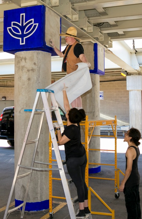 "Brother Mark Elder, C.M., with the aid of former DePaul students Christina Morris and Emanuel Cajijas, right, hangs a series of murals, Saturday, Aug. 6, 2016, on the massive concrete pillars supporting the CTA's ""L"" station and tracks at Fullerton. Throughout the spring 2016 quarter and into the summer, Brother Mark and his Mural Class students created several portraits and historically-themed murals that will eventually wrap the support columns, which runs right through DePaul's Lincoln Park Campus. The murals depict many prominent, historical figures that have made an impact on DePaul University. (DePaul University/Joel Dik)"