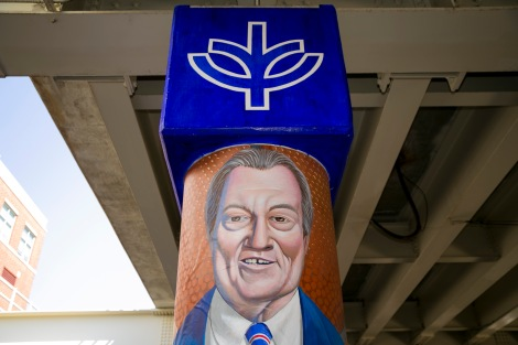 "A series of murals Monday, Aug. 8, 2016, on the massive concrete pillars supporting the CTA's ""L"" station and tracks at Fullerton. Throughout the spring 2016 quarter and into the summer, Brother Mark Elder, C.M., and his Mural Class students created several portraits and historically-themed murals that will eventually wrap the support columns, which runs right through DePaul's Lincoln Park Campus. The murals depict many prominent, historical figures that have made an impact on DePaul University. (DePaul University/Joel Dik)"