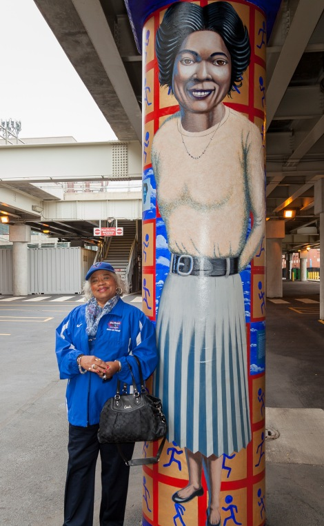 "Mabel ""Dolly"" Landry Staton, DePaul alumna, olympian and track star, next to a mural depicting her likeness as part of the ""Little School Under the 'L, 'under the L'"" public art project, Saturday, Oct. 15, 2016. The murals, which wrap around pillar's underneath the CTA's Fullerton 'L' stop, depict important historical figures from DePaul's past. Figures in include legendary DePaul basketball coach Ray Meyer, civil rights activist and judge Benjamin Hooks, Staton, and the first women graduates of DePaul. The five murals installed are part of a larger project to add at total of 24 over the next several years, with more prominent DePaul figures.  (DePaul University/Joel Dik)"