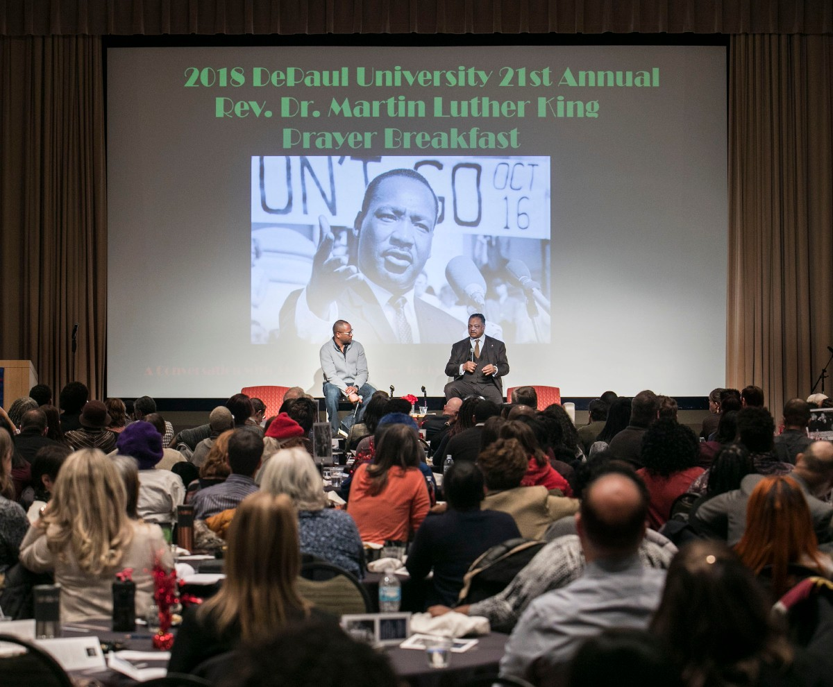A large seated crowd listen to the Rev. Jesse L. Jackson Sr. and Horace Hall, an associate professor in DePaul's College of Education, in front of a projected photo of the Rev. Dr. Martin Luther King Jr.