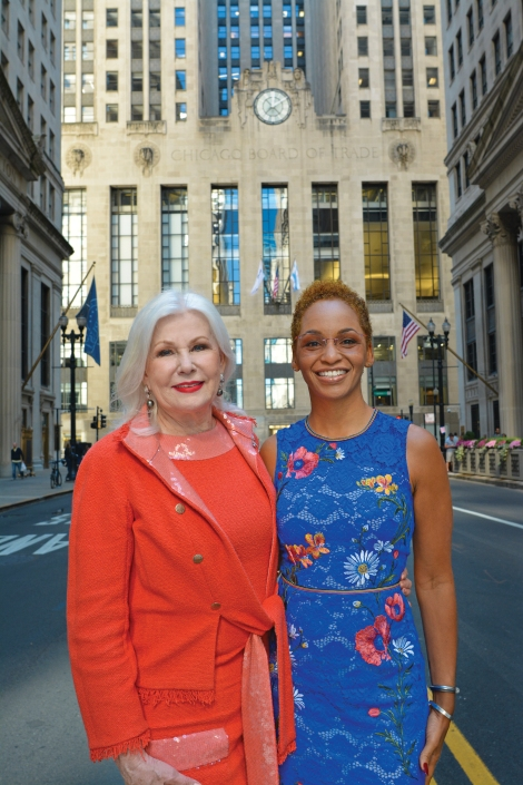 Two female DePaul alumni, one Caucasian and one African American, stand on LaSalle Avenue in Chicago in the heart of the financial district.