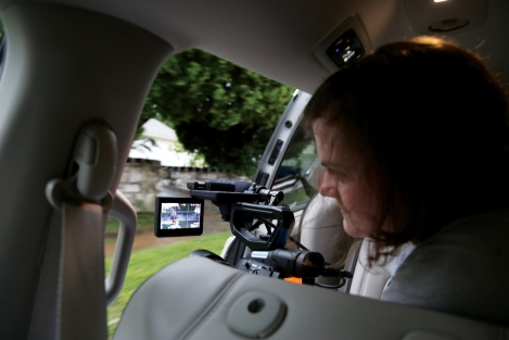 A female student films out the side of a moving van to capture a photo of a client jogging.