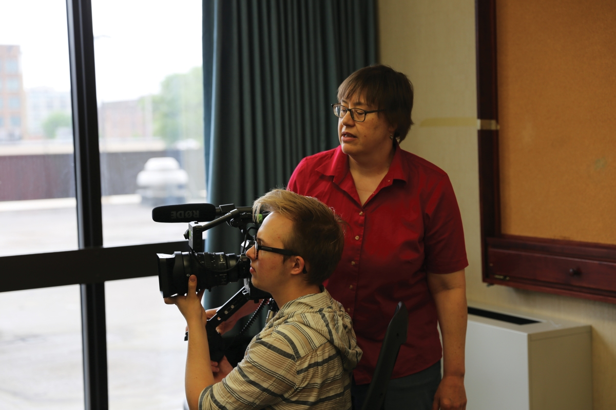 A Caucasian woman with short brown hair and glasses stands behind a male student who is focusing a camera out a window.