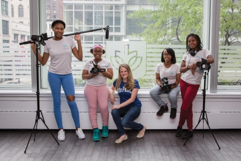 Four teenage African-American women with filmmaking equipment pose with a Caucasian adult woman who is one of their instructors.