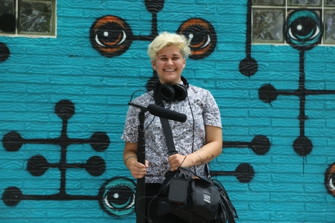 Young Caucasian woman with short blonde hair holding sound recording equipment in from of a blue wall mural.