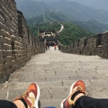 Pair of feet in tennis shoes at the top of a steeply sloping set of stairs on the Great Wall of China.