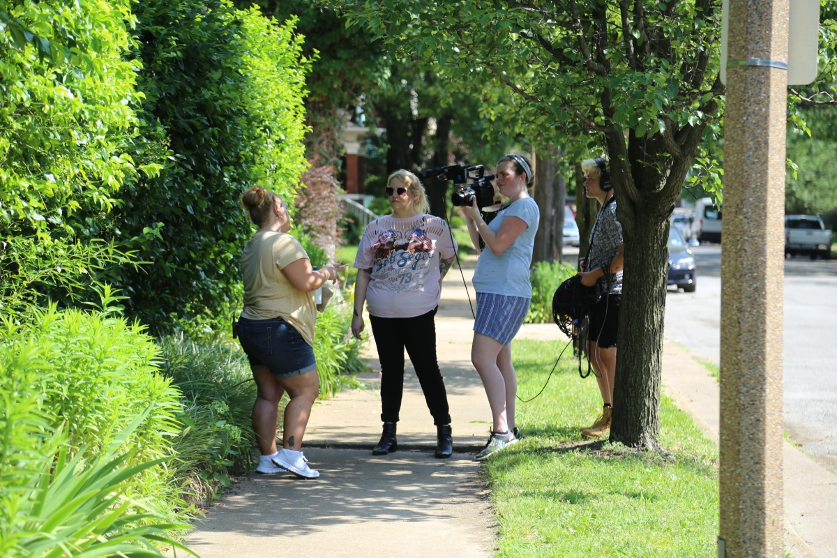 Three female students with camera equipment film a female client of Depaul USA on a sidewalk in a on a sunny, green street.