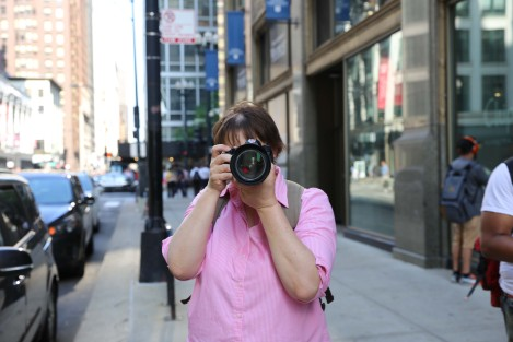 Caucasian woman in pink shirt aims camera right toward the photographer.