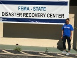 Young female African American alumna in blue DePaul t-shirt standing next to banner reading FEMA-State Disaster REcover Center.