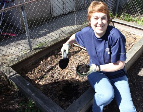 Associate editor Kris Gallagher had the soil in her raised-bed garden and yard tested by students at DePaul. Kris is sitting on the edge of her garden box, holding soil in one hand and a trowel full of soil in the other.